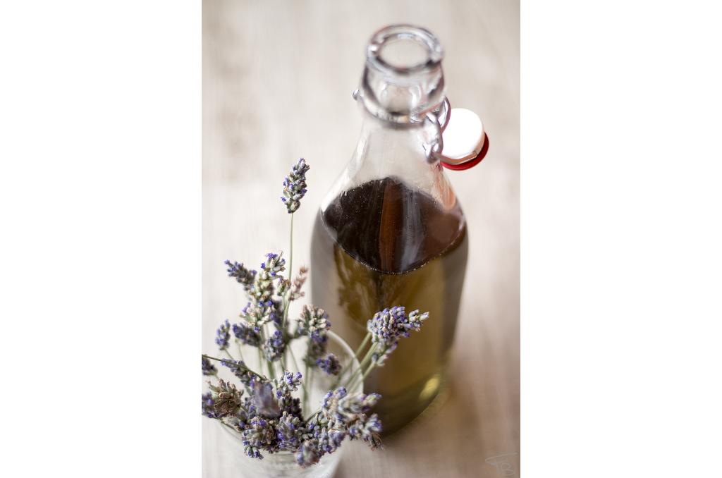 bicchiere di vetro con fiori freschi di lavanda e bottiglia di vetro con lo sciroppo