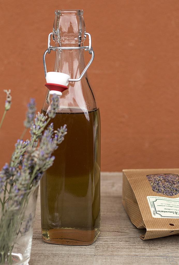 bottiglia di vetro di sciroppo alla lavanda con bicchiere con i fiori e una busta di fiori essiccati edibili