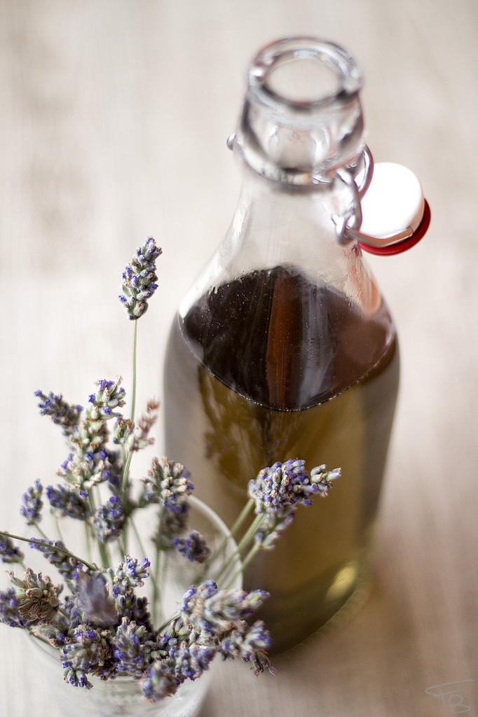 bicchiere di vetro con fiori freschi di lavanda e bottiglia di vetro con lo sciroppo alla lavanda