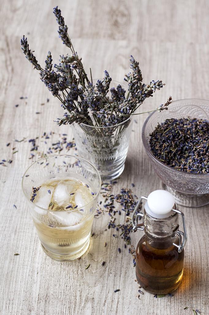 Piccola bottiglia di vetro contenente lo sciroppo alla lavanda, bicchiere con l'infuso di sciroppo alla lavanda, fiori di lavanda secchi