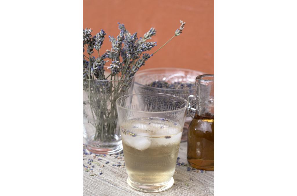 Piccola bottiglia di vetro contenente lo sciroppo alla lavanda, bicchiere con l'infuso di sciroppo alla lavanda, fiori di lavanda secchi su sfondo rosso mattone