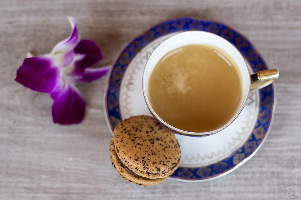 una tazzina antica di caffe' bollente ripresa dall'alto. appoggiata su un piano di legno grezzo gigio chiaro con un fiore viola di orchidea appogiato a lato.
