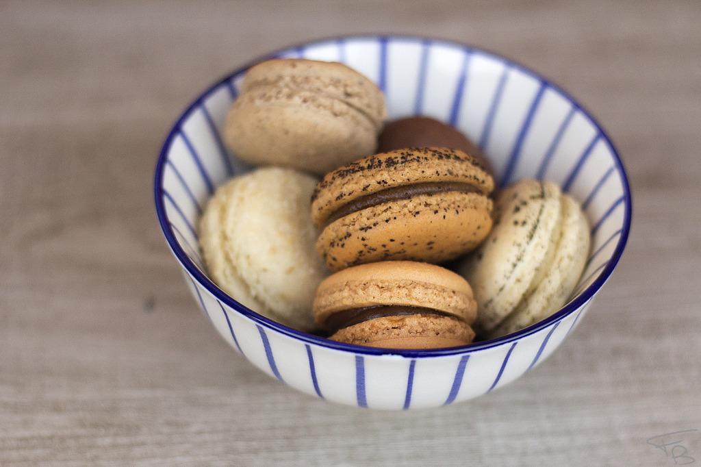 una coppetta di ceramica giapponese, bianca con sottili righe bli scuro ripiena di piccoli dolcetti francesi realizzati con farina di mandorle amare