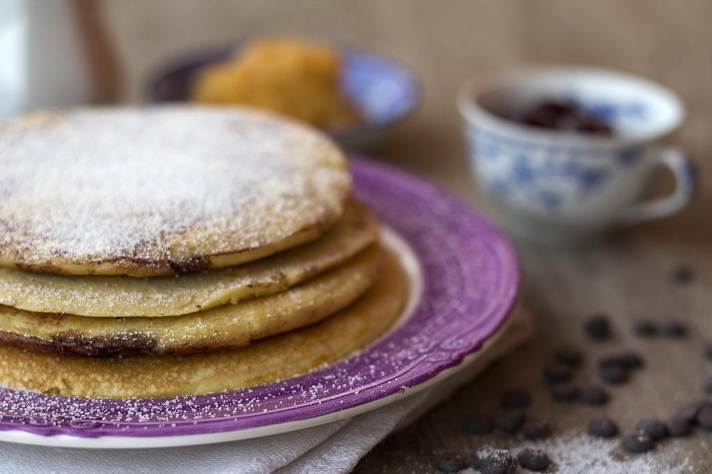 pancakes su un piatto di colore viola brillante con gocce di cioccolato