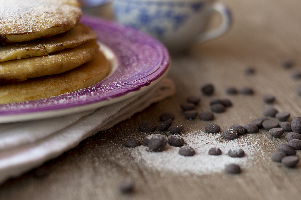 gocce di cioccolato in primo piano e pancakes di lato
